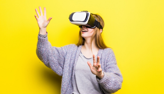Teenage girl with virtual reality headset on yellow background